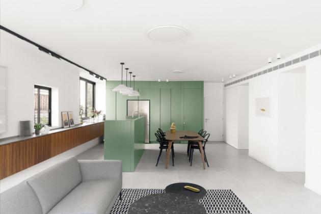 Podél zdi za ostrůvkem architekti umístili skříňky zořechového dřeva vedoucí až do obývací části.