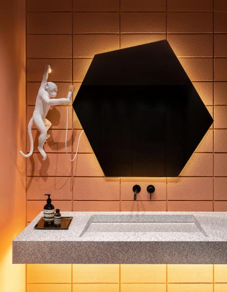 Koupelna pro hosty je záměrně navržena v jasných barvách. Originálním doplňkem je svítidlo Monkey Lamp značky Seletti.