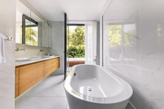 Zkaždé obytné místnosti je separátní vstup naterasu azahradu, která lemuje byt vetvaru písmene U. Koupelna, kterou využívají majitelé, se tak pyšní luxusním výhledem, velkým množstvím denního světla ataké jednoduchým přístupem kvenkovní whirlpool vaně