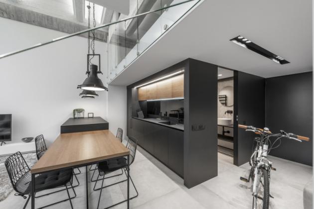 Interiér má monochromatický vzhled s teplými neutrálními odstíny doplněný přírodními materiály jako je dřevo, beton, kov a sklo