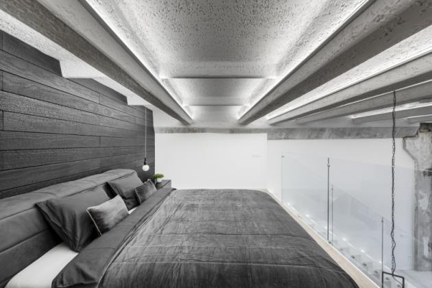 Ložnice je umístěna nahoře, pocit soukromí zajišťují závěsy. Zajímavostí je obklad stěny dřevem accoya pocházející z trvale udržitelných zdrojů.