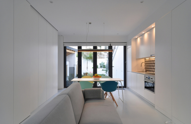 Jednotvárnost místy příjemně narušuje barevný nábytek a tradiční prvky (ručně vyráběné obklady na hlavní fasádě, vzorované keramické dlaždice na terasách a kuchyních).