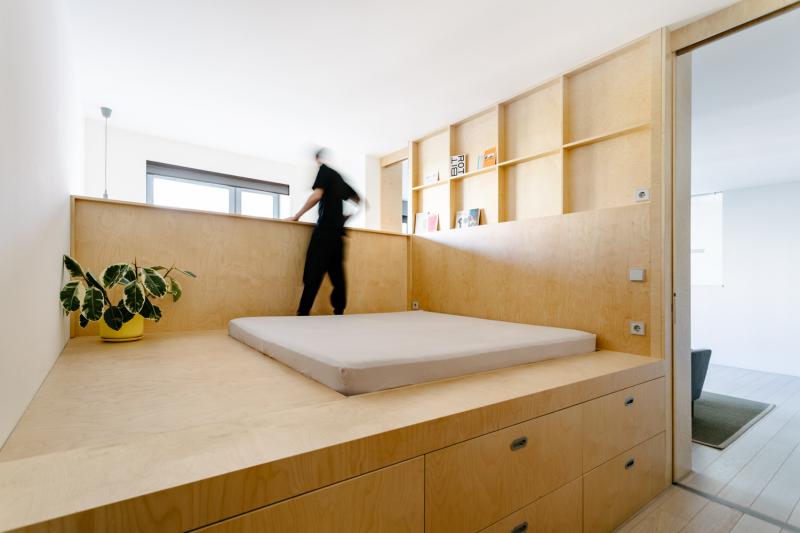 Ložnice a pracovna se sloučily, dělí se o jedno okno, avšak každá zóna má svůj vlastní vstup. Vizuálně jsou rozděleny nízkou stěnou, která odděluje vyvýšenou část postele od pracovny.