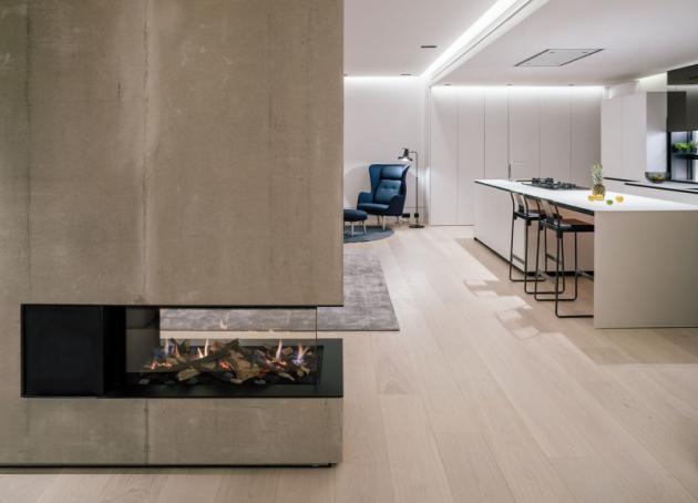 Optické rozdělení centrální místnosti architekti vyřešili pomocí kuchyňského ostrůvku a krbu.