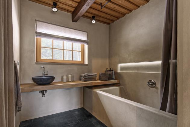 Koupelna nabídla dostatek prostoru k umístění vyzděné vany ošetřené stěrkou, která je i na stěnách. Podlahu kryje kámen. Na dřevěné desce je posazeno betonové umyvadlo (Gravelli). Osvětlená nika umožňuje praktické odložení nezbytností pěkně po ruce