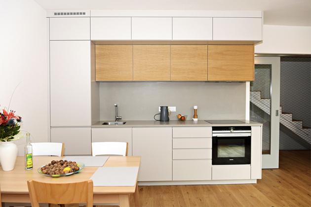 Malá kuchyň vevelkém domě vprovedení šedý matný lak sfrézovaným J profilem vkombinaci sdubovou dýhou nahorních skříňkách. Pracovní deska azástěna jsou zkeramiky. Zvýšené spodní skříňky napřání zákazníků