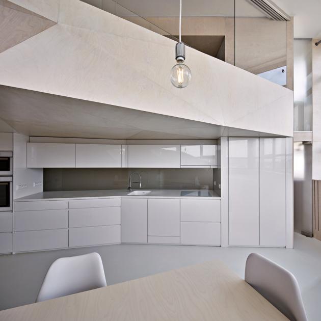 Minimalistická kuchyně má povrchovou úpravu lakem svysokým leskem, která dobře odráží světlo