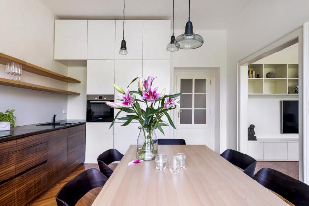 Tmavý nábytek vkuchyni je zhotoven namíru zkouřové eukalyptové dýhy apracovní plocha je vytvořena tenkou probarvenou kompaktní deskou (Polyrey). Pracovní plochu osvětluje pásek sLED diodami. Bílý nábytek je vyroben zlakované MDF desky. Kuchyň je vybavena černým granitovým dřezem sbaterií (Schock), indukční varnou deskou avestavnými spotřebiči