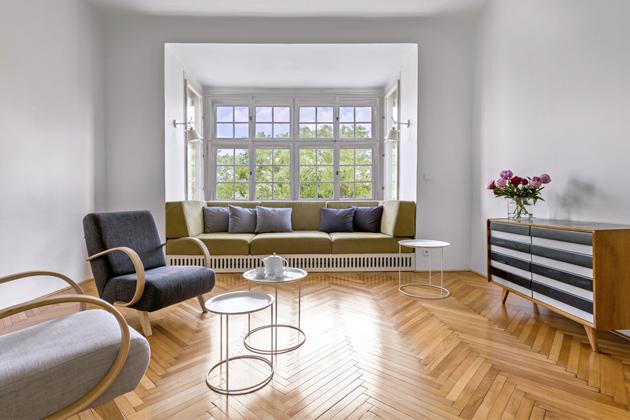 Dochované původní prvky bytu – špaletová okna, dveře abukové parkety vhodně doplňují restaurovaná křesla astará komoda vretro stylu. Prostor pro pohodlnou sedací soupravu vyrobenou namíru poskytl hluboký arkýř. Postranách ji doprovázejí ikonické lampy Tolomeo (Artemide)