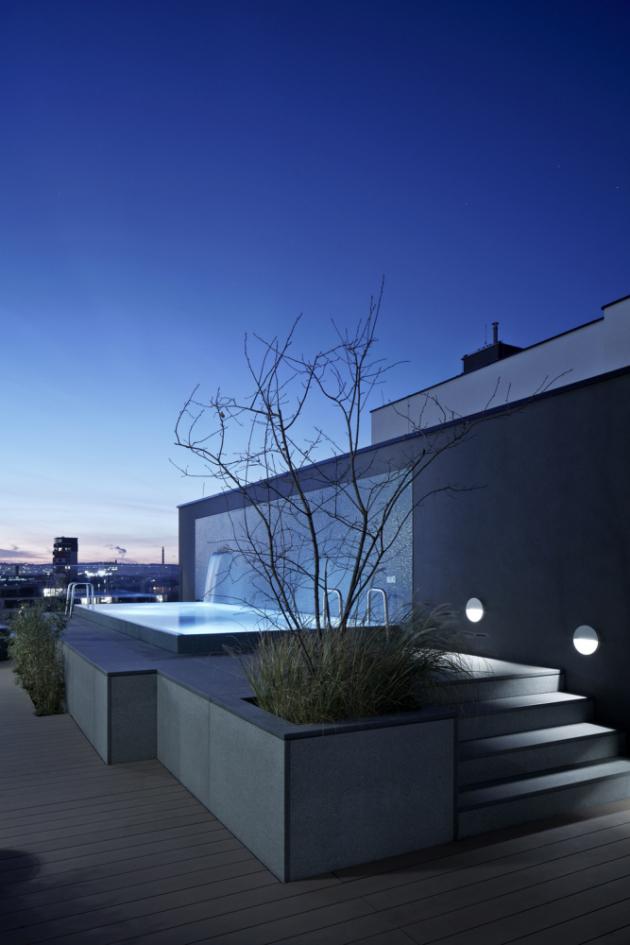 Součástí projektu je také terasa zbazénem, nakterou se vstupuje zložnice aobývacího pokoje, asauna vedruhém patře. Celková rozloha venkovních prostor je 212 m²