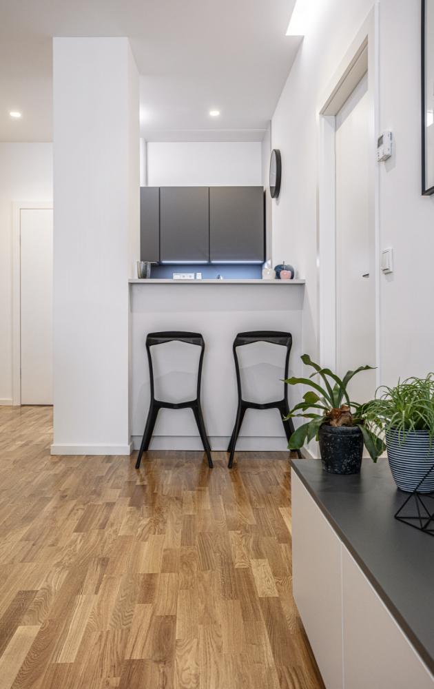 Kuchyň je odobývacího prostoru oddělena zvýšeným pultem advěma plastovými barovými židlemi