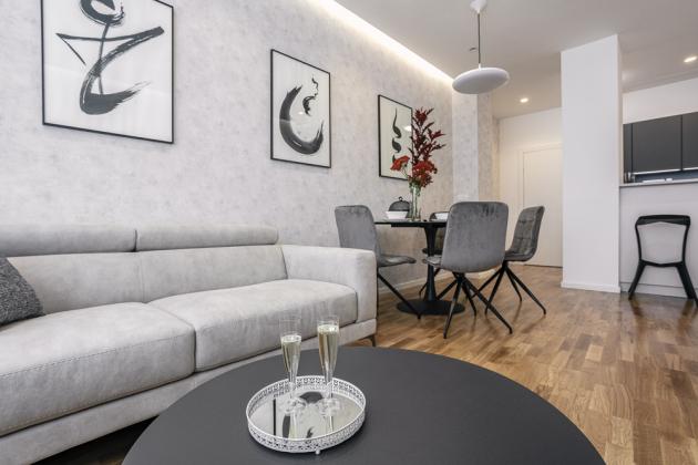 Kulatý jídelní stůl je obklopen čalouněnými, prošívanými židlemi (Texo) nakovových podnožích. Podlahu kryje du