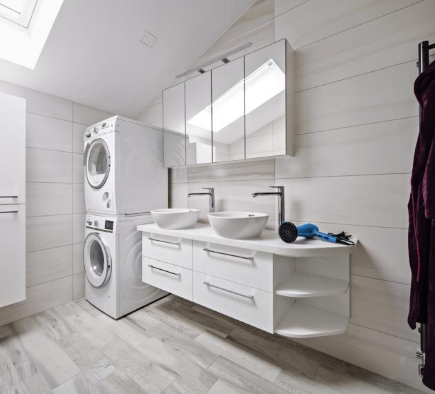 Vevětší koupelně vpatře je vana isprchový kout. Zpraktických důvodů sem majitelé umístili také pračku asušičku. Dekor mramoru příjemně zateplují obklady se vzorem surového dřeva