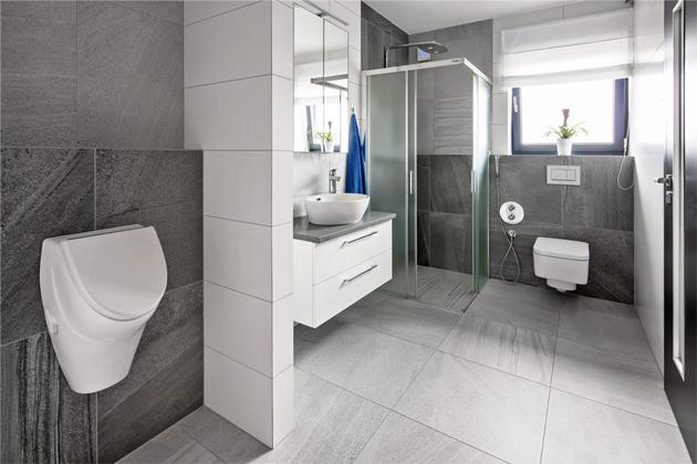 Velká koupelna v přízemí,  kterou využívají ipříležitostné návštěvy, je vybavená sprchovým koutem, toaletou apraktickým bidetem