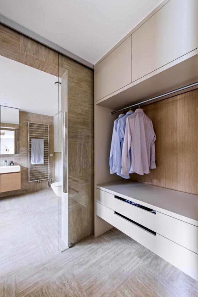 Nábytek v šatně, která je od koupelny oddělena skleněnou posuvnou příčkou, byl vyroben na míru v polomatné lakované úpravě v truhlárně architektonického studia de.fakto