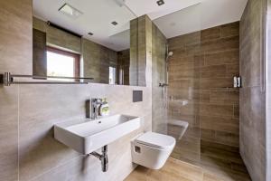 Také v menší koupelně, do které se vstupuje přímo z pokoje pro hosty, zvolili majitelé prostorově úsporné řešení sprchového koutu typu walk-in. K odkládání předmětů slouží spodní okraj mělké niky se zrcadlem