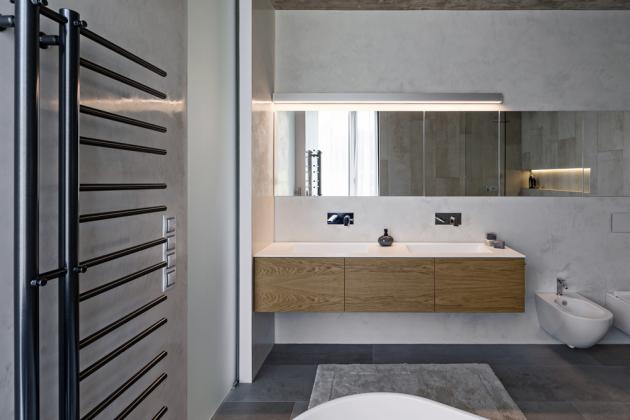 Řada zrcadlových skříněk odráží denní i umělé světlo, takže celá koupelna působí ještě prostorněji. Vzdušnosti prospívá i minimum zařizovacích předmětů