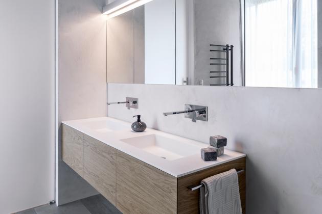 Zrcadlové skříňky jsou zapuštěné tak, že lícují se stěnou. Do desky na široké skříňce jsou zapuštěna dvě umyvadla doplněná nástěnnými bateriemi