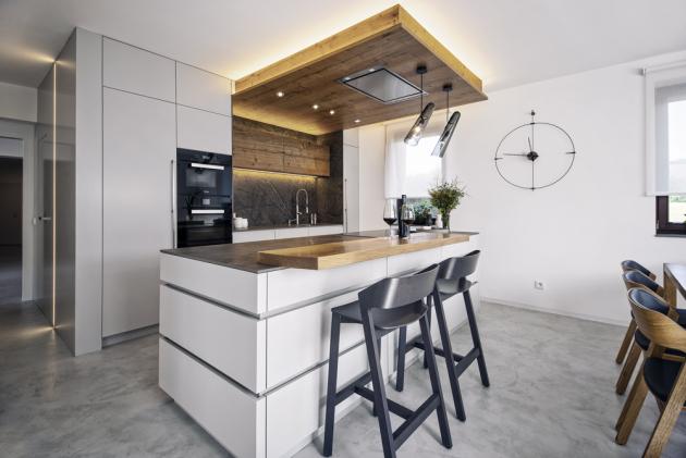 Kuchyni namíru zdobí dvířka lakovaná světle šedým lakem, který se vybíral ještě před zahájením všech prací nazákladě vzorku stěrkové podlahy. Základní barva podlahy je tak shodná slakem dvířek. Pracovní deska iobklad zadní stěny jsou zkeramického materiálu Dektone. Architektka vybavení kuchyně doplnila ospotřebiče značky Miele
