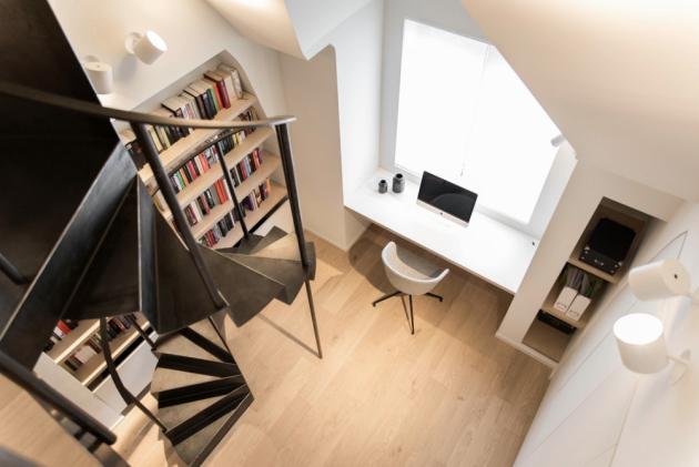 Ložnici v prvním patře přeměnili na pracovnu s knihovnou. Odtud vede točité kovové schodiště do druhého patra