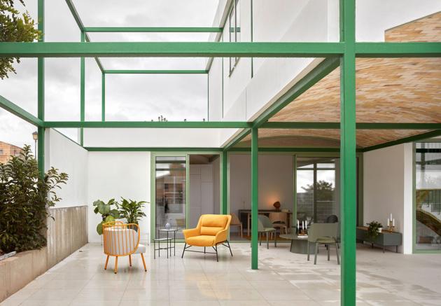 Zelená ocelová mříž slouží jako konstrukční rám a je klíčovým estetickým bodem designu