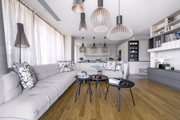 Linie nábytku kopíruje tvar zdi apostupně mění svou funkci podle přechodu jednotlivými prostory – zpředsíňové stěny kombinující botníky, sedačku aúložné skříňky až napodobu skříněk vkuchyni. Vobývacím pokoji slouží především gramofonovým deskám