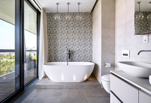 Ústředním prvkem koupelny je zaoblená vana (Badeloft) spodlahovou baterií Freedom (Ravak), stojící napodstavci se zapuštěnými bodovými světly, aby vevečerním světle mohla být zdůrazněna linie vany jako šperku, apřitom nabídnuto intimní osvětlení podpořené závěsnými světly od J.Lawrence. Stěna vedle vany je vytápěná aobložená keramikou s3D texturou, připomínající látku vesmetanových tónech smodrými ašedými nitkami. Právě sohledem natento obklad byl zvolený materiál naokna pro celý tento byt. Tkanina typu in-between nabízí přechod mezi záclonou azávěsem, kdy dokonale propouští světlo, apřitom izajišťuje nezbytnou intimitu