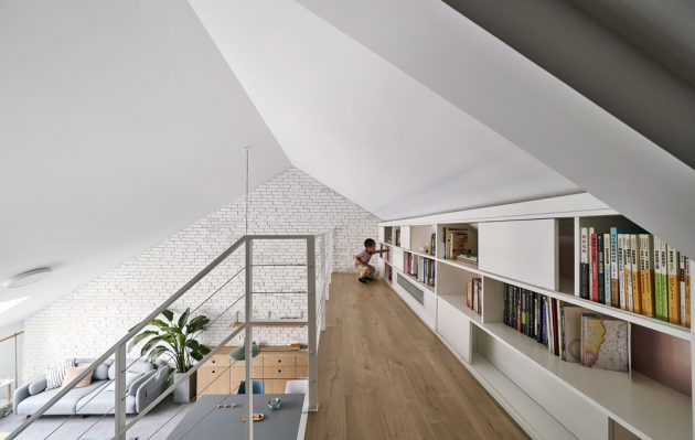 Pocelé délce galerie je vestavěná knihovna sotevřenými auzavřenými policemi. Vzhledem kezkosené stěně jde onejlepší možné využití jinak hluchého prostoru