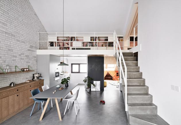 Robustní betonové schodiště je barevně sladěné spodlahou vhlavní obytné místnosti. Šedé abílé plochy vinteriéru převládají, zjemňují je akcenty vpastelových odstínech