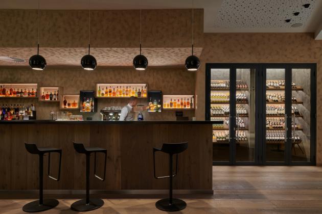 Lamelami z kolekce dřevěných vícevrstvých krytin Kährs Grande (dekor Dub Citadelle), které dováží společnost Kratochvíl parket profi, byl v restauraci Bar and Lounge Passage obložen bar