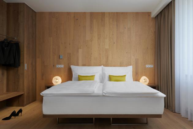 Standardní pokoje hotelu Passage jsou laděny do méně výrazných barev a struktur v podobě Dubu bílého CD z kolekce Kährs Atelier, dováží KPP, i v těchto pokojích však nezůstaly podlahy jen ve vodorovné poloze na zemi a interiéry doplnily i designové lampy Jaroslava Bejvla mladšího.