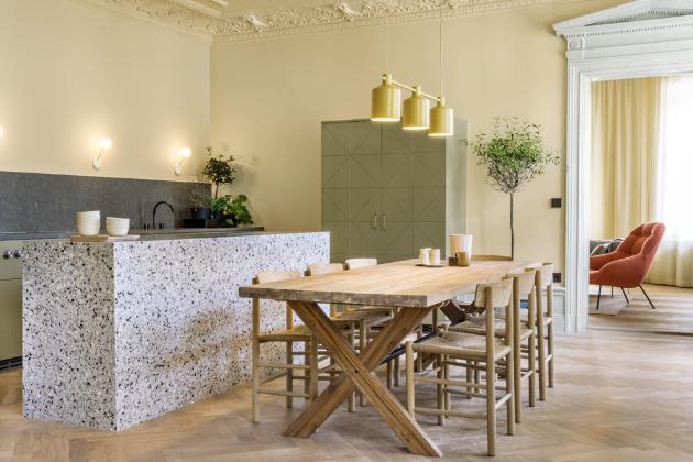 Interiér je plný zdařilých kombinací časem prověřených prvků se současnými trendy. Minimalistický kuchyňský ostrůvek je z terazza a dekor na míru vyrobeného nábytku je inspirován vzorem původních parket. Židle J39 navrhl Borge Mogensen v roce 1947 pro výrobce Fredericia, osvětlení Silo Trio nad jídelním stolem navrhli autoři realizace z Note Design Studia pro výrobce Zero