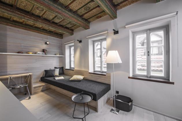 Sedací nábytek slouží současně také jako plnohodnotné lůžko s kvalitní matrací a úložným prostorem. Nízký stolek vedle jako noční stolek a vysoký, s židlí na kolečkách, supluje pracovnu