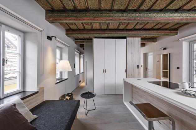 Nábytek z bílého lamina je zhotoven na míru. Podlaha z běleného dubu slouží částečně také jako obklad jedné stěny. Repasovaná okna je možné přistínit roletami. Kuchyňská sestava nábytku zahrnuje běžné úložné prostory, vestavnou chladničku s mrazničkou, troubu i prostornou niku určenou pro drobné spotřebiče