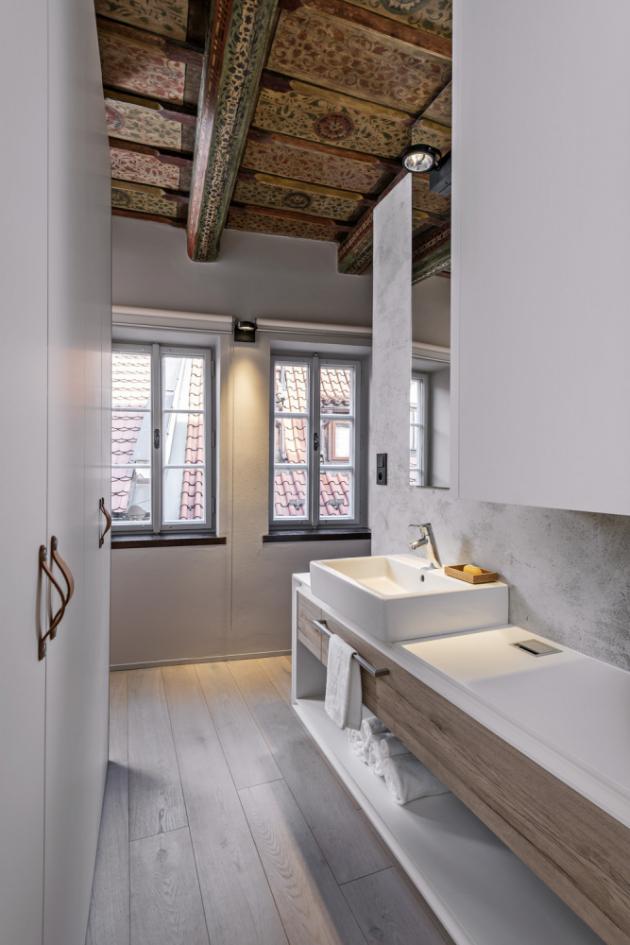 Koupelna je otevřená, volně průchozí z chodby a prakticky dosažitelná z WC i ložnice. Sestava koupelnového nábytku nabízí úložný prostor s dvěma zásuvkami a ukrývá také bojler na teplou vodu. Skříňka je osazena keramickým umyvadlem Vero (Duravit) se stojánkovou baterií (Hansgrohe) a opatřena nerezovou průchodkou pro kabely ke kryté zásuvce
