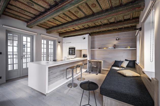 V tomto bytě není nic montováno do stropu, vše spočívá na nábytkových konstrukcích propojených mezi sebou. I vodicí tyč posuvných dveří je kotvena do protější zdi. Byt je vytápěný elektrickým podlahovým kabelem. Velkoryse koncipovaný ostrůvek poskytl prostor nejen široké indukční desce, myčce a dřezu (Franke), ale i místo pro každodenní stolování na barových židlích z jedné strany a pro úložné zásuvky z opačné