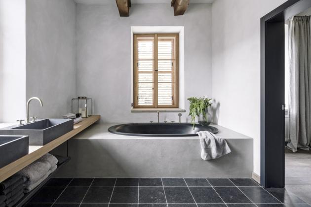 V koupelně se o pozornost dělí černá, do soklu s omyvatelnou stěrkou zapuštěná vana s betonovými umyvadly (Gravelli) a italské mosazné baterie (Fantini Rubinetti)
