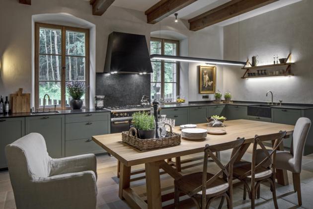 Lomený odstín zelenošedé barvy staví na odiv na míru zhotovená kuchyňská sestava dubového nábytku doplněná zinkovanými spoji. Harmonické spojení podporuje i kamenná deska. Je vyrobena na míru stejně jako stůl a lavice. Kuchyň je vybavená dvěma dřezy, ledničkami a francouzským plynovým sporákem se širokou troubou