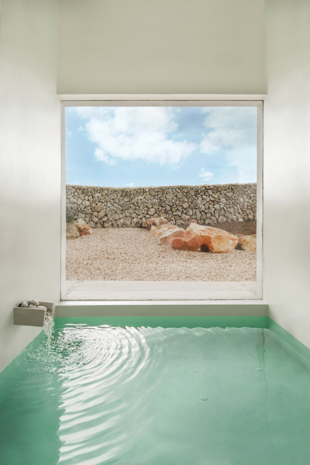 Tato mělká vodní nádrž s miniaturní fontánou zdobenou kameny se nachází před velkým oknem s výhledem do okolní krajiny.