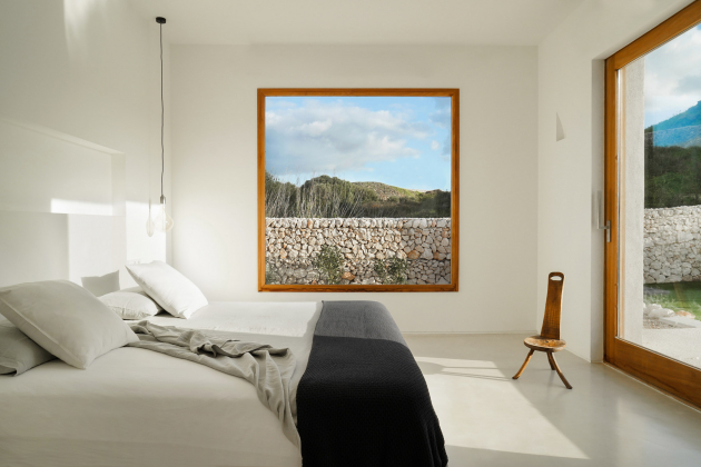 Interiér tvoří bílé stěny spodlahou ve světlém odstínu, nechybí akcenty dřeva a jednoduchý nábytek.