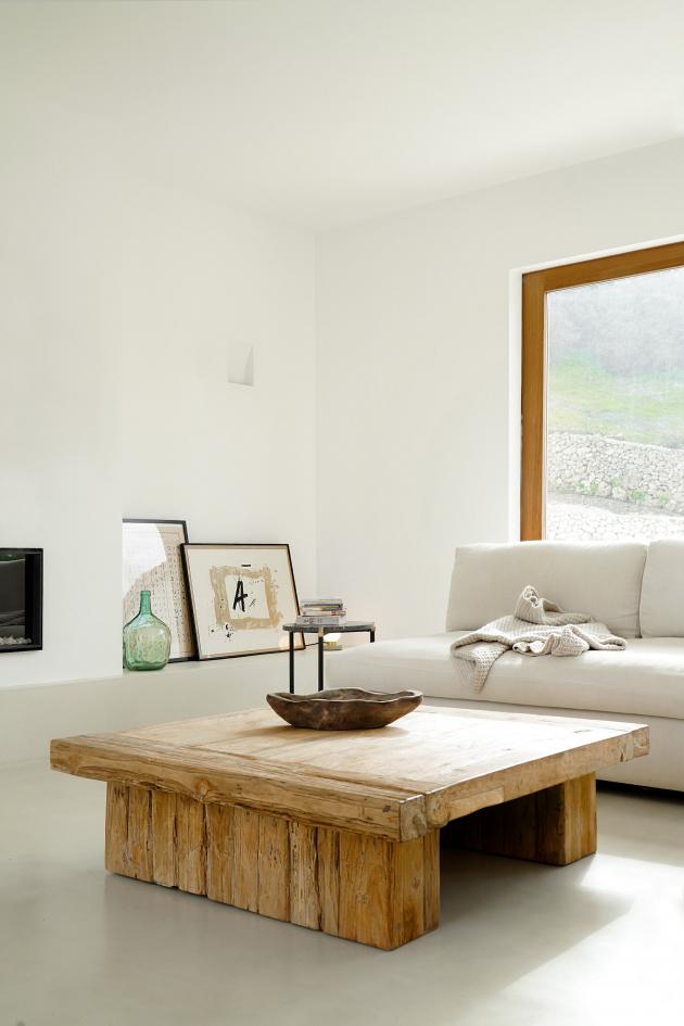 Obývacímu pokoji dominuje masivní dřevěný konferenční stolek vrustikálním stylu a sedací nábytek vbílé barvě.