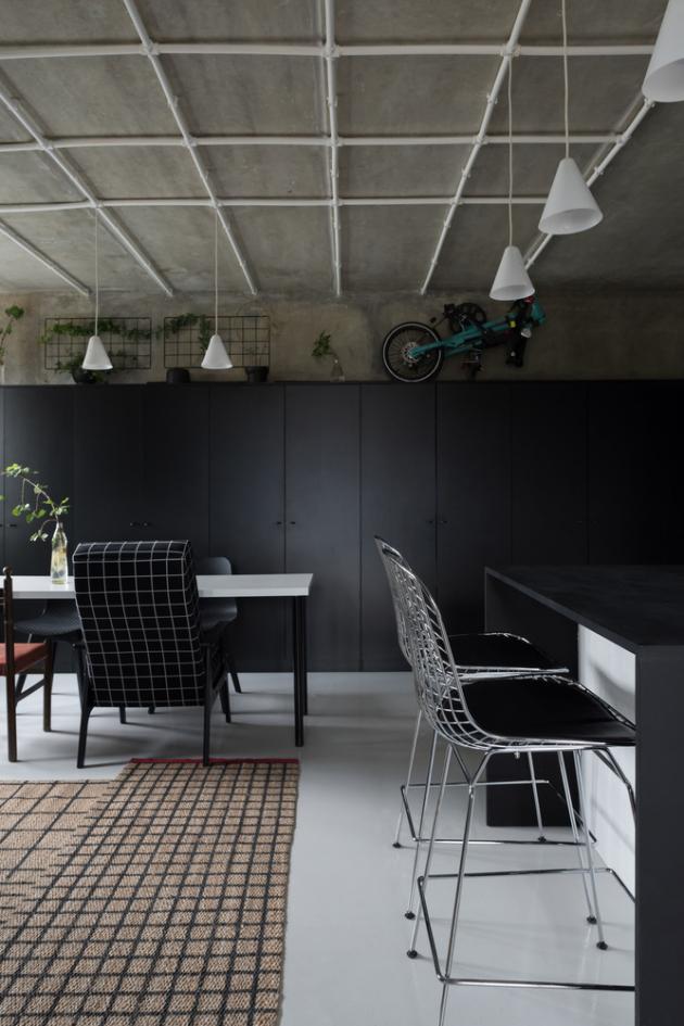 Otevřená část skuchyní je vybavena skříní a kuchyňským ostrůvkem včerné barvě.
