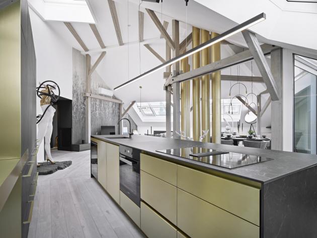 Kuchyňská sestava nábytku z tmavé dýhy a keramická pracovní deska příjemně kontrastují s mosaznými detaily