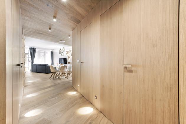 Zádveří je kompletně zhotoveno na míru a obloženo dubem. Bezfalcové dveře vedoucí do místností jsou téměř neviditelné. Stylově je dotvářejí i kliky (MaT)