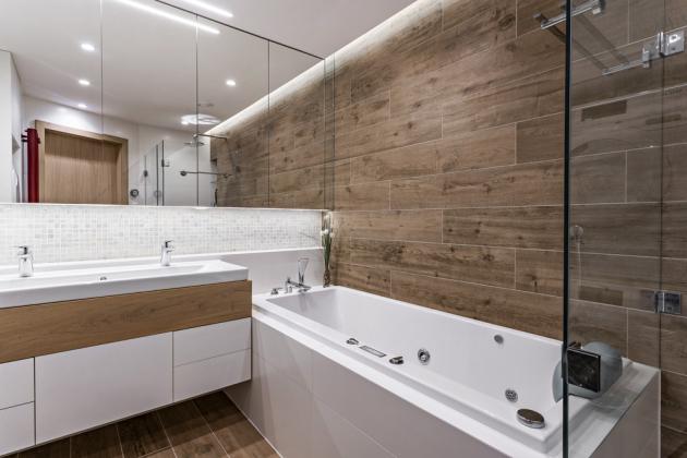 Koupelna je obložena skleněnou mozaikou Moon (Vidrepur) a imitací dřevěného obkladu, keramikou Essenziale Satinato (Marazzi). Komfort užívání podporuje prostorný sprchový kout, dvojumyvadlo Subway 2.0 (Villeroy Boch) a hydromasážní vana Subway (Villeroy Boch). Ze stejné kolekce je i závěsný klozet