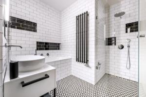 V koupelně je kromě vany bezbariérový sprchový kout s odtokovým žlábkem, velkou hlavovou a ruční sprchou a dvěma nikami