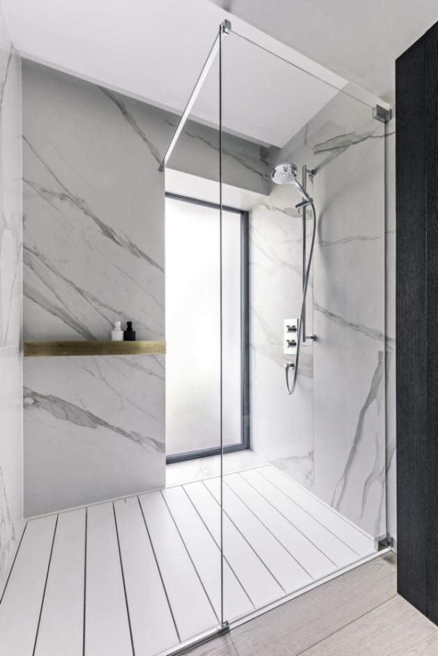 Stěna ve sprchovém koutě je obložena keramickými obklady Porcelanosa s dekorem mramoru