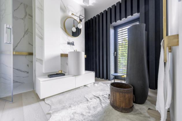 Příjemný kontrast tvoří v koupelnách obložení stěny hnědočerným dubovým dřevem, které dobře ladí s etno artefakty a měděnými prvky