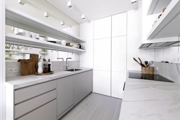 Kuchyň není nijak velká, ale dostatečně vyhoví přípravě snídaní i základnímu vaření. Součástí nábytku, zhotovenéhonamíru, je vestavěná chladnička s mrazničkou. Nechybí tu ani vestavěná užší myčka a horkovzdušná trouba. Rohy kuchyňské sestavy nábytku vyplňují praktické karusely a další vertikálně umístěné uskladňovací systémy. Barevný tón kuchyňského nábytku vychází z jemných barev žilkování podlahové krytiny, zhotovené z olejovaných dubových prken