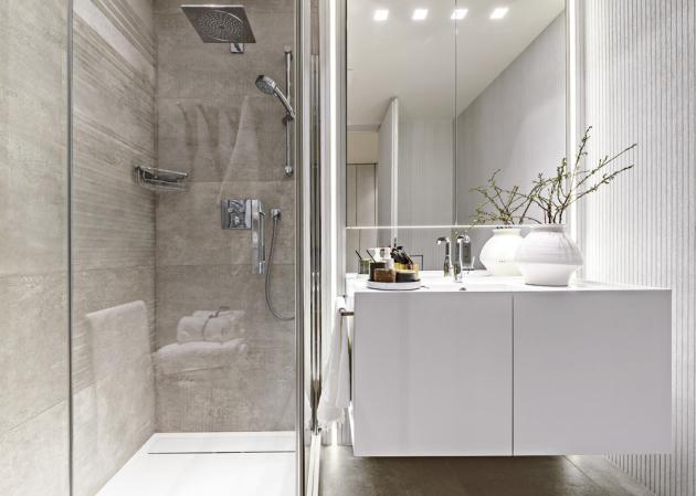 Koupelna je z větší části obložená lakovaným dubovým obkladem, do něhož jsou téměř neznatelně zapuštěny bezfalcové dveře. Zbytek je obložen velkoformátovou dlažbou 60 × 60 cm (Porcelanosa). Podle autorského návrhu Martina Franka je velmi důmyslně anamíru zhotoveno corianové umyvadlo s opačnou hranou. Je upravené tak, aby voda nezatekla do skříňky, a doplněné stojánkovou baterií (Grohe). Lehce zapuštěná zrcadlová skříňka nabízí dostatek úložného místa a opticky násobí prostor. Nebylo třeba bidetu, tady kraluje elektronicky ovládaný moderní klozet (Geberit)
